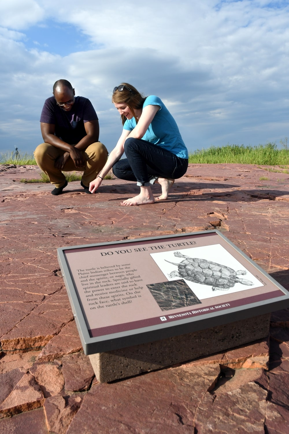 Kamil and Amy search for a carving of a turtle at the Jeffers Petroglyphs site